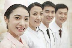 Glimlachende Gezondheidszorgarbeiders die, camera, China bekijken zich op een rij bevinden die Stock Foto