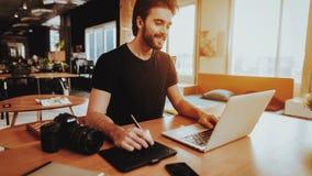 Glimlachende Grafische Ontwerper Works op Laptop binnen royalty-vrije stock foto