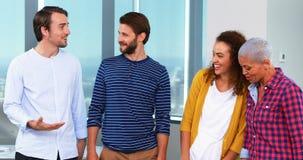 Glimlachende grafische ontwerpers die met elkaar interactie aangaan stock videobeelden