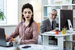 Glimlachende grijs-haired arbeider die aandachtig op zijn vrouwelijke collega kijken royalty-vrije stock fotografie