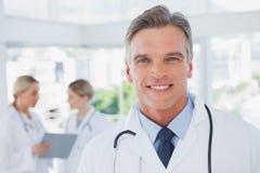 Glimlachende grijze haired arts die zich in zijn bureau bevinden Royalty-vrije Stock Foto