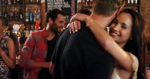 Glimlachende groep vrienden die terwijl het hebben van alcohol op elkaar inwerken stock video