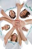 Glimlachende groep vrijwilligers die omhoog hun handen opstapelen stock afbeeldingen