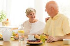 Glimlachende grootmoeder die ontbijt met haar echtgenoot in mor eten royalty-vrije stock foto's