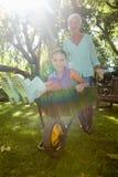 Glimlachende grootmoeder duwende kleindochter in kruiwagen stock afbeeldingen