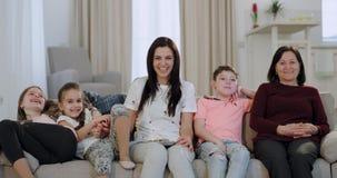Glimlachende grote aantrekkelijke oma haar dochter en kleinkinderen voor camere terwijl het letten van op de TV-zitting stock videobeelden