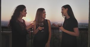 Glimlachende grote dames bij de partij op de penthousezolder, bij het balkon met verbazende zonsondergangmening drinken zij glasw stock video