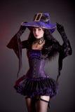 Glimlachende heks in purper en zwart gotisch Halloween-kostuum Royalty-vrije Stock Foto