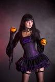 Glimlachende heks in purper gotisch Halloween-kostuum Stock Foto's