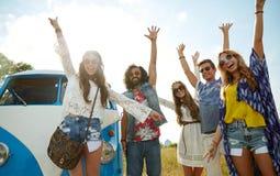 Glimlachende hippievrienden die pret over minivan auto hebben stock foto's