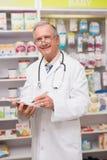 Glimlachende hogere arts die op klembord schrijven Stock Fotografie