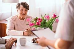 Glimlachende hogere dame die aan haar arts in het verpleeghuis luisteren royalty-vrije stock fotografie