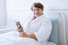 Glimlachende hogere dame die mobiele telefoon houden terwijl het zitten in het ziekenhuisbed royalty-vrije stock foto
