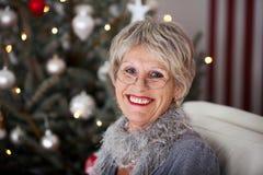 Glimlachende hogere dame voor de Kerstboom royalty-vrije stock afbeelding