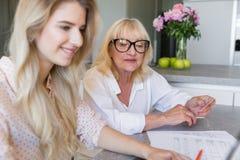 Glimlachende hogere grootmoeder met haar kleindochter die online betalen royalty-vrije stock afbeelding