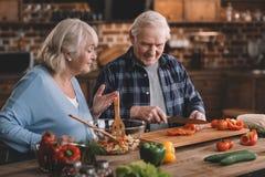 Glimlachende hogere man en vrouw die salade samen maken stock fotografie