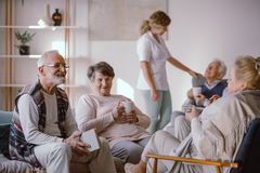 Glimlachende hogere mens die aan andere ingezetenen van het pensioneringshuis spreken royalty-vrije stock afbeelding