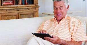 Glimlachende hogere mens die digitale tablet in woonkamer gebruiken stock video