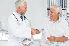 Glimlachende hogere patiënt en artsen het schudden handen Royalty-vrije Stock Foto's