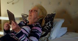 Glimlachende hogere vrouw die digitale tablet binnen op bed in slaapkamer 4k gebruiken stock footage