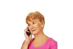 Glimlachende hogere vrouw die door telefoon spreken Stock Afbeeldingen