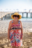 Glimlachende Hogere vrouw die hoed dragen bij strand Stock Afbeeldingen
