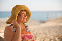 Glimlachende Hogere vrouw die hoed dragen bij strand Royalty-vrije Stock Fotografie