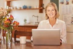 Glimlachende hogere vrouw met laptop bij houten lijst stock fotografie
