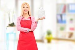 Glimlachende huisvrouw die schort dragen en een zak geschoten houden thuis Royalty-vrije Stock Afbeeldingen