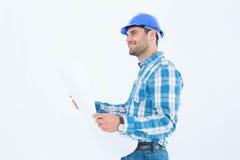 Glimlachende ingenieur die weg terwijl het houden van blauwdruk kijken Royalty-vrije Stock Afbeeldingen