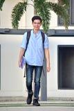 Glimlachende Jeugdige Aziatische Jongensstudent With Notebooks Walking stock afbeelding