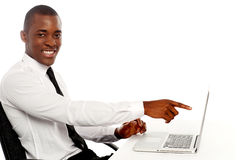 Glimlachende jonge Afrikaan die op laptop het scherm wijst op royalty-vrije stock foto