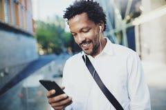 Glimlachende jonge Afrikaanse Amerikaanse mens in hoofdtelefoon die bij zonnige stad lopen en aan muziek op zijn mobiel genieten  stock afbeeldingen