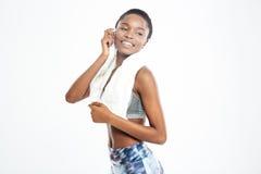 Glimlachende jonge Afrikaanse Amerikaanse sportvrouw met handdoek op haar hals Stock Foto