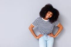 Glimlachende jonge Afrikaanse Amerikaanse vrouw die zich tegen grijze achtergrond met handen op heupen bevinden royalty-vrije stock afbeeldingen
