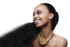 Glimlachende jonge Afrikaanse Amerikaanse vrouw met zeer lang natuurlijk haar stock fotografie
