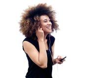 Glimlachende jonge Afrikaanse vrouw die aan muziek luisteren stock afbeeldingen