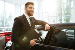 Glimlachende jonge autoverkoper die zich bij het handel drijven bevinden stock foto's