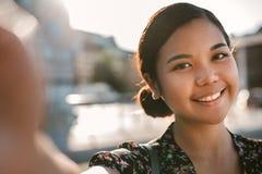 Glimlachende jonge Aziatische student die zich buiten het nemen van een selfie bevinden stock fotografie
