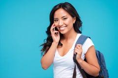 Glimlachende jonge Aziatische vrouw met rugzak die op cellphone spreken stock afbeelding