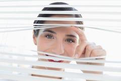 Glimlachende jonge bedrijfsvrouw die door zonneblinden gluren stock afbeeldingen