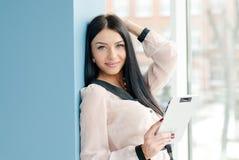 Glimlachende jonge bedrijfsvrouw die tabletpc met behulp van terwijl status ontspannen dichtbij venster op haar kantoor Royalty-vrije Stock Afbeelding