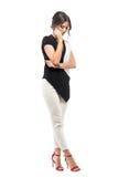 Glimlachende jonge bedrijfsvrouw in kostuum die op de telefoon spreken die neer eruit zien royalty-vrije stock fotografie
