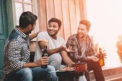 Glimlachende jonge bier drinken en vrienden die terwijl het maken van barbecue spreken royalty-vrije stock afbeelding
