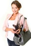 Glimlachende jonge die vrouw met Chihuahua in een zak op wit wordt geïsoleerd Royalty-vrije Stock Foto's