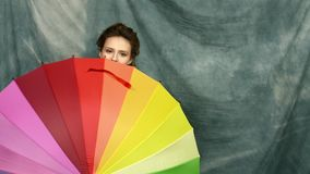 Glimlachende jonge donkerbruine vrouw met multi-coloured paraplu stock videobeelden