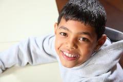 Glimlachende jonge etnische schooljongen die grijze hoodi draagt Stock Fotografie
