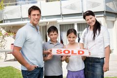 Glimlachende jonge familie die nieuw huis koopt Stock Afbeelding