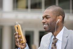 Glimlachende jonge gelukkige mens die aan muziek op cellphone luisteren royalty-vrije stock afbeeldingen