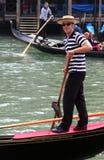 Glimlachende jonge gondelier in traditionele kleding op zijn gondel op Grand Canal Royalty-vrije Stock Foto